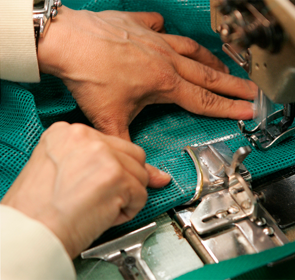 associate using sewing machine to attach parts of a jacket
