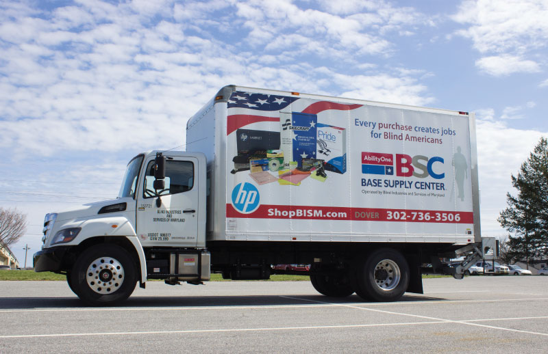 BSC truck with advertisement for the BSCs and ShopBISM.com on the side parked outside a store